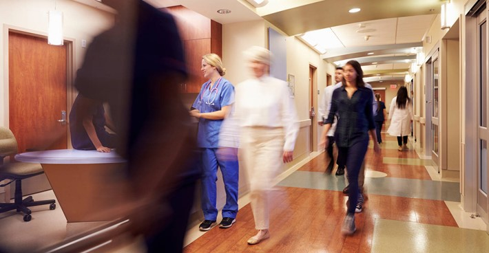 Busy hospital with blurred figures moving through a reception area
